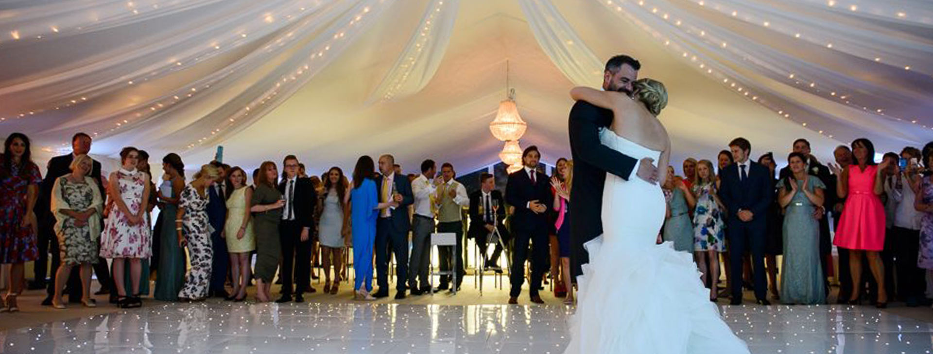 bride and groom first dance in a wedding marquee
