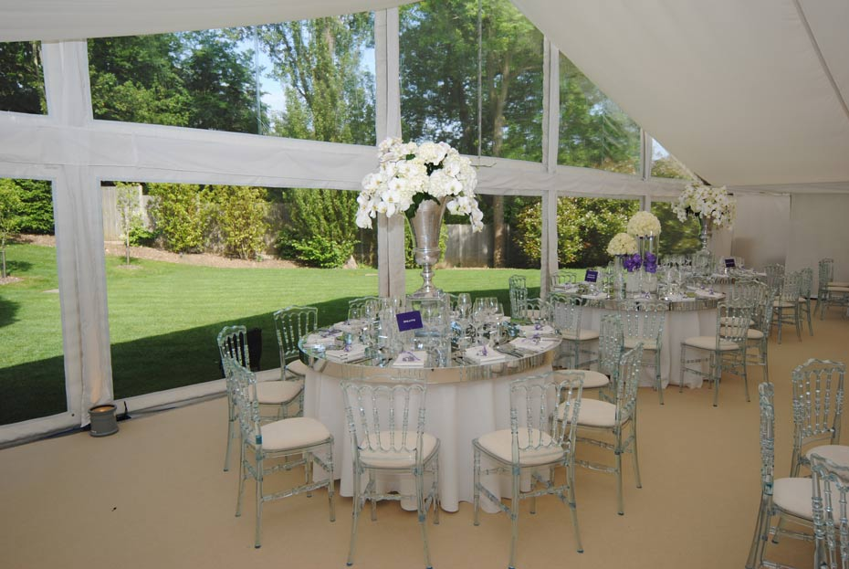 wedding decorations in a marquee with floor to ceiling windows