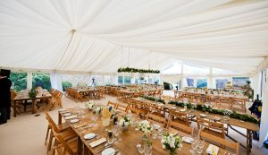 Rustic themed wedding marquee with ivory pleated lining