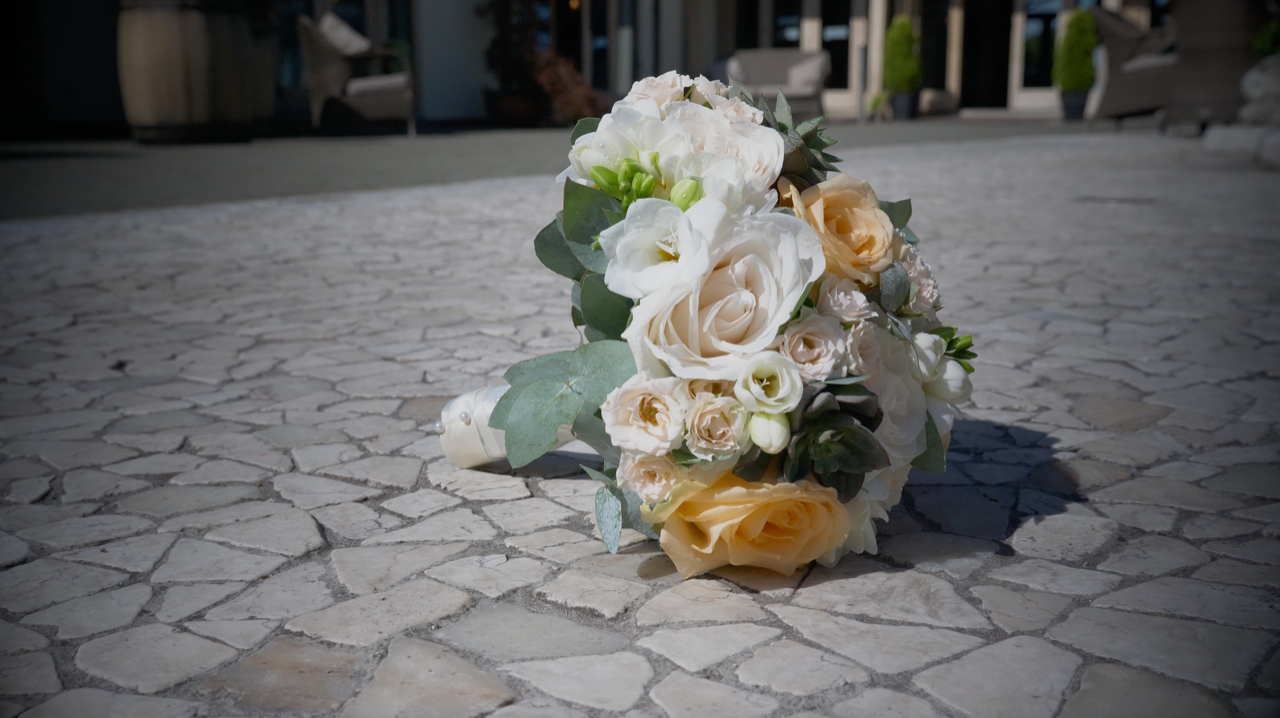 Beautiful wedding bouquet with roses on a cobbled street