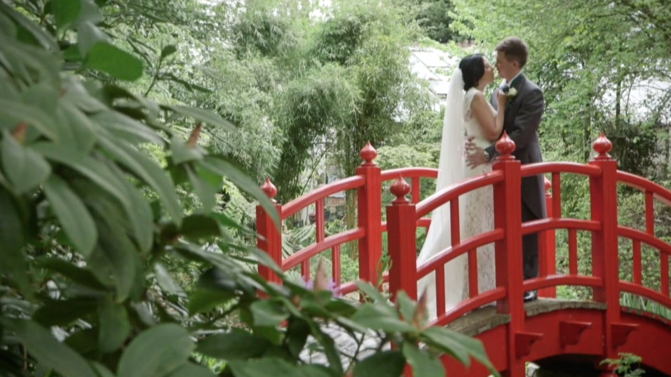 Wedding couple kissing on a bridge