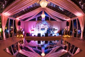 Glass marquee set up for party with live music and mirrored dance floor