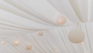 Ivory pleated lining in wedding marquee