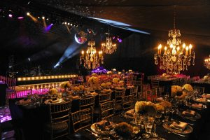 Elegant gold and black themed dining area in party marquee