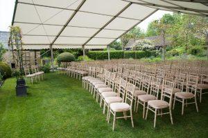 Outdoor wedding ceremony in open marquee