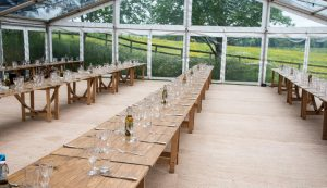 Trestle tables for rustic themed wedding in glass style marquee