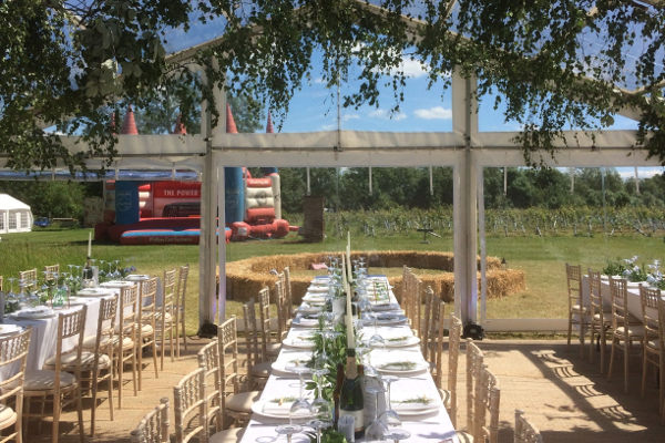 trestle tables and lime wash chairs in clear roof marquee