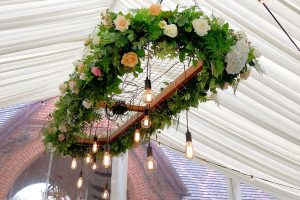Pendant drop light in marquee dressed with fresh flowers and foliage