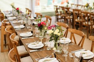 Marquee with dining facilities of rustic trestle and cross back chair